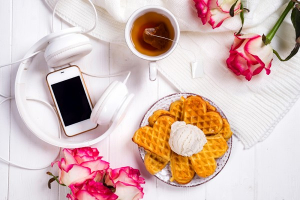 "alt=""morning schedule with tea, waffle, headphones, iphone and flowers"""