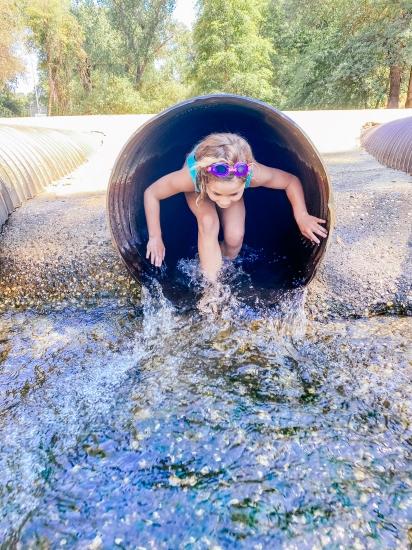 child going through drainpipe at western gateway park