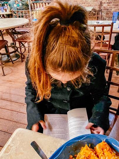 little girl reading and eating enchiladas